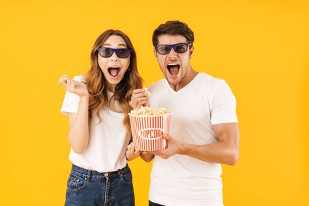Portrait of delighted couple man and woman in 3D glasses rejoicing while standing together with popcorn bucket isolated over yellow background