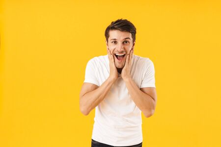 Photo of delighted man in basic t-shirt smiling at camera and grabbing his face with hands isolated over yellow background