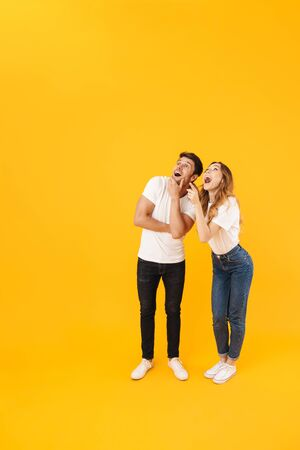 Full length portrait of young couple man and woman in basic t-shirts wondering while looking upward at copyspace isolated over yellow background