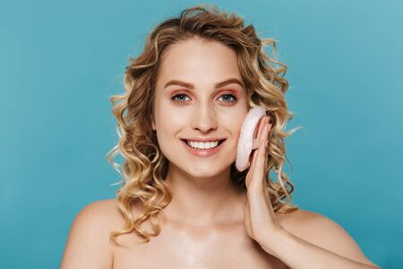 Image of charming shirtless woman 20s with curly blond hair applying makeup with powder puff isolated over blue background