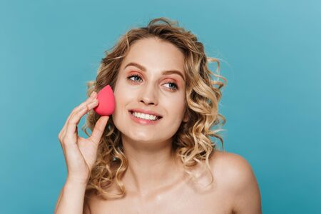 Image of pleased half-naked woman applying makeup with sponge isolated over blue background