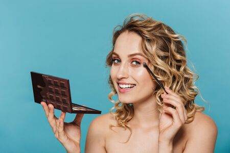 Image of caucasian half-naked woman applying makeup with cosmetic pallet and brush isolated over blue background