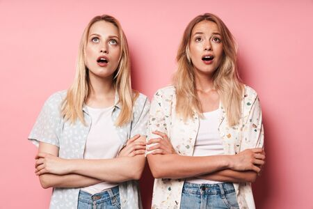 Image of emotional shocked pretty blondes women friends posing isolated over pink wall background. Banco de Imagens