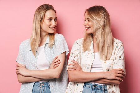 Two attractive smiling blonde girls wearing summer outfit standing isolated over pink background, arms folded, looking at each other Banco de Imagens