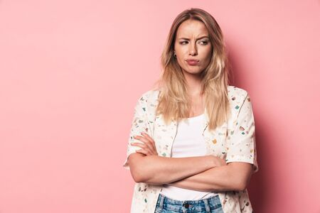 Picture of a displeased young blonde cute girl posing isolated over pink wall background with arms crossed.