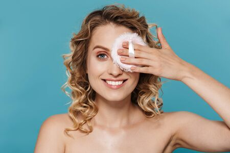 Image of nice half-naked woman applying makeup with powder sponge isolated over blue background