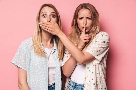 Picture of serious girls women friends sisters isolated over pink wall background covering mouth showing silence gesture.