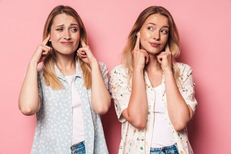 Picture of displeased girls women friends sisters isolated over pink wall background covering ears because of loud.