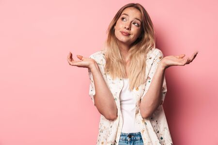 Portrait of a beautiful confused young blonde woman standing isolated over pink background, shrugging shoulders 스톡 콘텐츠