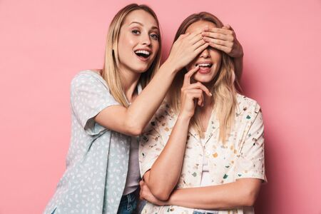 Picture of cheerful girl covering eyes of her woman friend sister isolated over pink wall background. Banco de Imagens