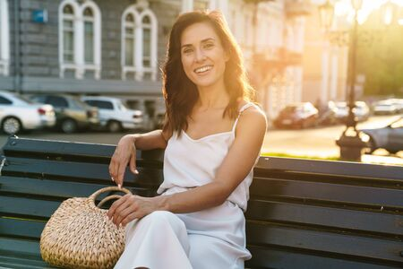 Portrait of happy woman in summer dress smiling and looking at camera while sitting on bench outdoors