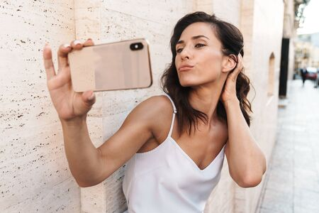 Portrait of alluring pleased woman making kiss face and taking selfie photo on smartphone while standing over wall on city street