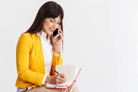 Image of a beautiful young business woman posing isolated over white background talking by mobile phone writing notes. 스톡 콘텐츠