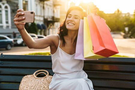 Portrait of happy woman in summer dress taking selfie photo on cellphone with shopping bags while sitting on bench outdoors