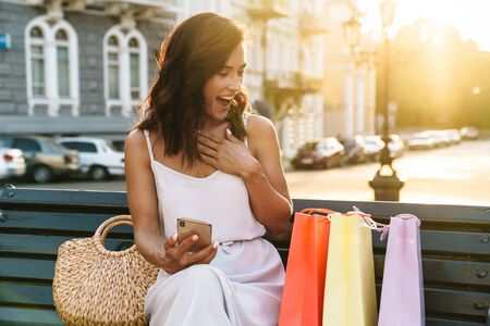 Portrait of excited woman in summer dress laughing and holding cellphone while sitting on bench outdoors with shopping bags