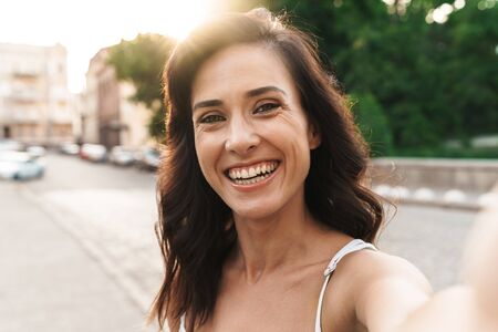 Portrait of pretty woman smiling and taking selfie photo while walking on city street