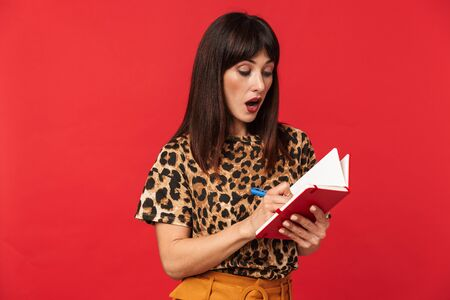 Image of a beautiful shocked young woman dressed in animal printed shirt posing isolated over red background writing notes in notebook. 스톡 콘텐츠
