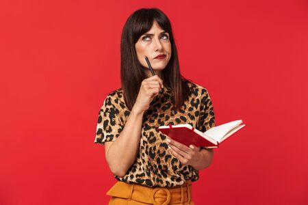Photo of thoughtful brunette woman 30s dressed in stylish outfit looking upward and writing notes in planner book isolated over red background 스톡 콘텐츠