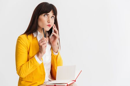 Image of a beautiful young confused business woman posing isolated over white background talking by mobile phone writing notes.