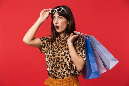 Image of a beautiful excited young woman dressed in animal printed shirt posing isolated over red background wearing sunglasses holding shopping bags.
