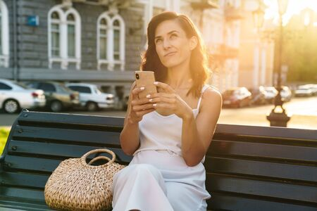 Portrait of charming woman in summer dress thinking and holding cellphone while sitting on bench outdoors 版權商用圖片