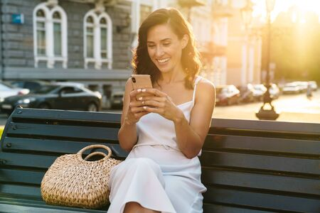 Portrait of cheerful woman in summer dress laughing and holding cellphone while sitting on bench outdoors