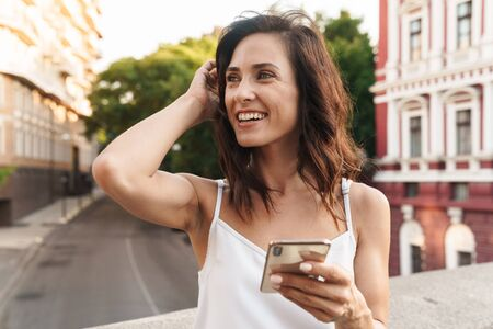 Portrait of caucasian woman smiling and typing on smartphone while standing on bridge with city street background