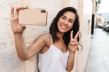 Portrait of smiling pleased woman taking selfie photo on smartphone and gesturing peace sign while standing over wall on city street