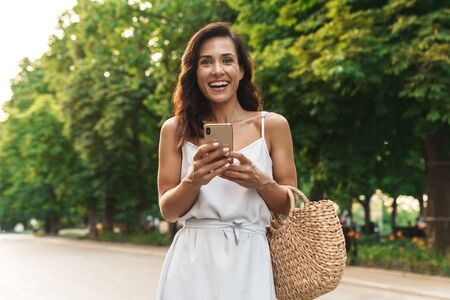 Portrait of lovely woman in summer dress smiling and holding cellphone while walking through green boulevard