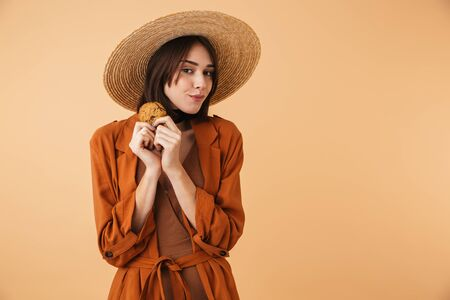 Beautiful young woman wearing straw hat and summer outfit standing isolated over beige background, eating chocolate chip cookie