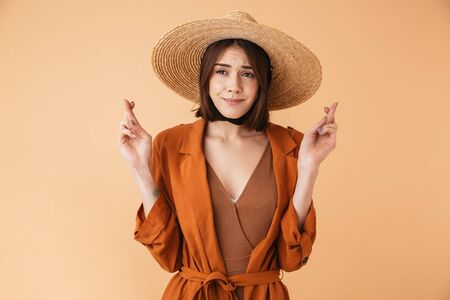 Beautiful young woman wearing straw hat and summer outfit standing isolated over beige background, fingers crossed Stok Fotoğraf