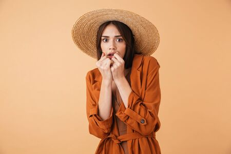 Beautiful scared young woman wearing straw hat and summer outfit standing isolated over beige background Stok Fotoğraf