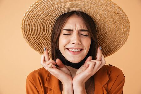 Beautiful young woman wearing straw hat standing isolated over beige background, holding fingers crossed for good luck