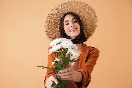 Beautiful young woman wearing straw hat and summer outfit standing isolated over beige background, holding camomile bouquet 스톡 콘텐츠