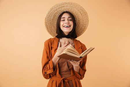Beautiful young woman wearing straw hat and summer outfit standing isolated over beige background, reading book