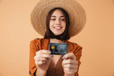 Beautiful young woman wearing straw hat and summer outfit standing isolated over beige background, showing plastic credit card