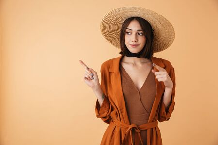 Beautiful young woman wearing straw hat and summer outfit standing isolated over beige background, presenting copy space