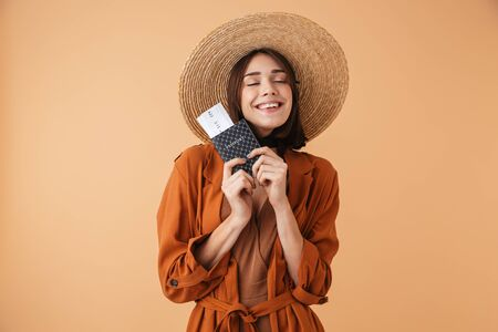 Beautiful young woman wearing straw hat and summer outfit standing isolated over beige background, holding passport with flight tickets Stock Photo