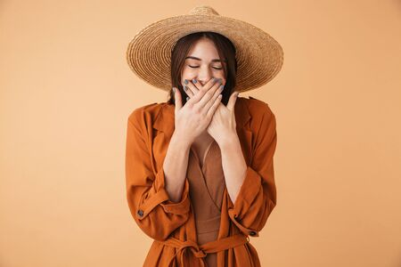 Portrait of a beautiful young woman wearing straw hat standing isolated over beige background, laughing
