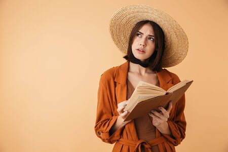 Beautiful pensive young woman wearing straw hat and summer outfit standing isolated over beige background, reading a book