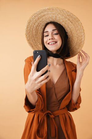 Beautiful young woman wearing straw hat and summer outfit standing isolated over beige background, taking a selfie