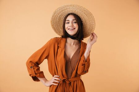 Beautiful young woman wearing straw hat and summer outfit standing isolated over beige background, posing