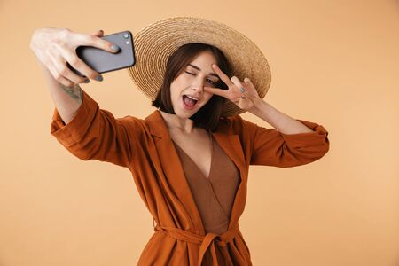 Beautiful young woman wearing straw hat standing isolated over beige background, taking a selfie, peace gesture