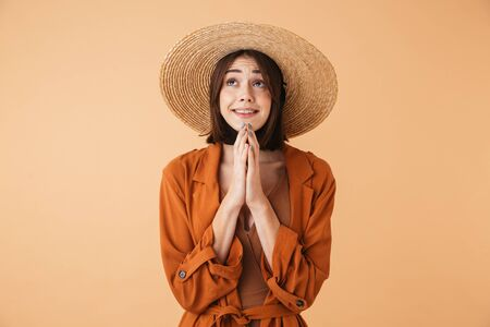 Beautiful young woman wearing straw hat and summer outfit standing isolated over beige background, begging Stok Fotoğraf