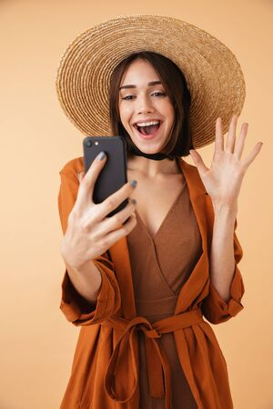 Beautiful young woman wearing straw hat standing isolated over beige background, taking a selfie Zdjęcie Seryjne