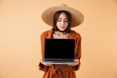 Beautiful young woman wearing straw hat standing isolated over beige background, showing blank screen laptop computer