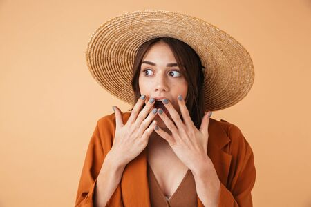 Beautiful shocked young woman wearing straw hat and summer outfit standing isolated over beige background Zdjęcie Seryjne