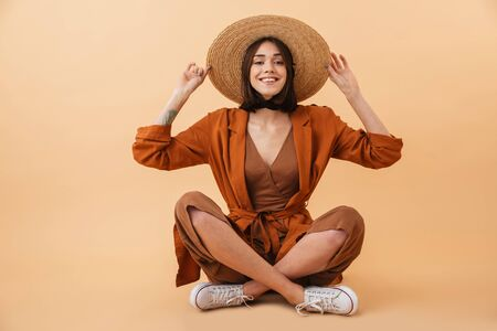 Beautiful young woman wearing straw hat and summer outfit sitting isolated over beige background, posing