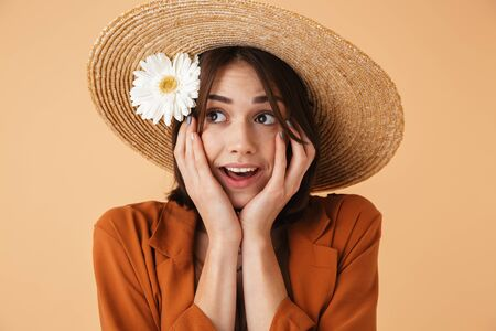 Beautiful young woman wearing straw hat and summer outfit standing isolated over beige background, posing with camomile flower 스톡 콘텐츠