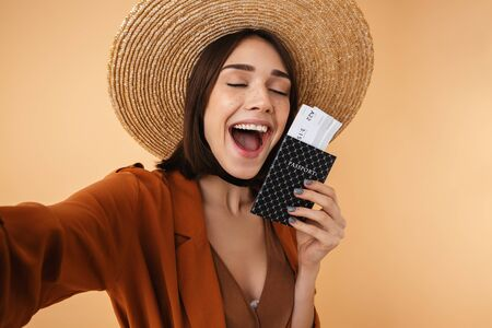 Beautiful young woman wearing straw hat and summer outfit standing isolated over beige background, taking a selfie while holding passport with flight tickets